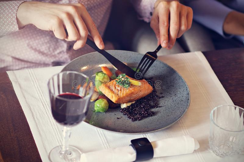 Couple eating romantic Dinner in a gourmet restaurant drinking wine and eating. Close-up of romantic Dinner in a gourmet restaurant couple drinking wine and stock photography