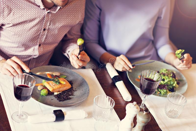 Couple eating romantic Dinner in a gourmet restaurant drinking wine and eating. Close-up of romantic Dinner in a gourmet restaurant couple drinking wine and royalty free stock images
