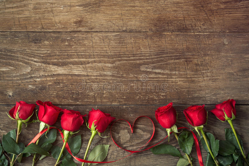 Close up on roses over wooden table with ribbon heart stock photos