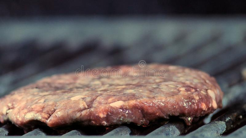 Close-up of a round burger patty is grilled and light smoke goes stock photography