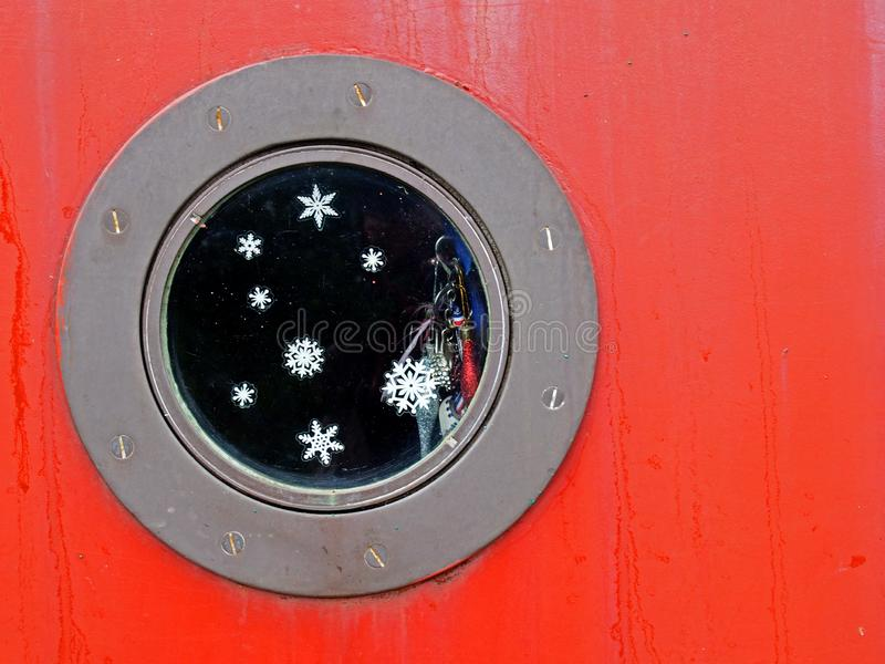 Close up of a round metal porthole on a red boat with snowflakes and glitter on the window and shiny charms hanging inside. A close up of a round metal porthole stock photo