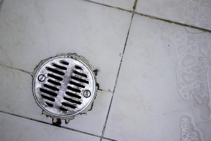 Round shower drain strainer made of stainless steel in a recently used shower. royalty free stock photography