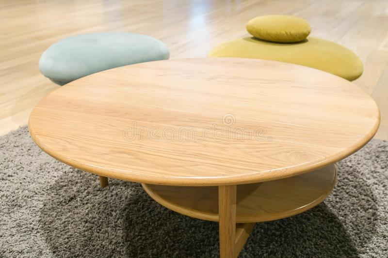 Round wooden table with colourful chair in wool rug stock photo