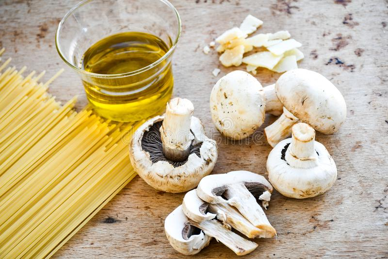 Italian Food ingredients. Close up of row spaghetti pasta , parmesan cheese, , olive oil extra vergin, and mushrooms .spaghetti and ingredients. Italian healthy royalty free stock photography