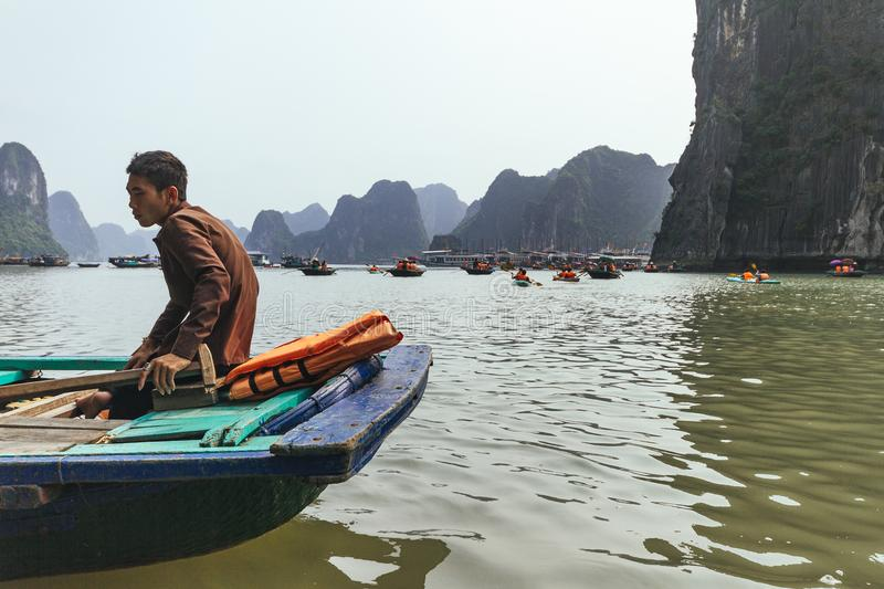 Close up rowing boats man sit in the boat that floating on emerald water with limestone islands in background in summer. royalty free stock photos