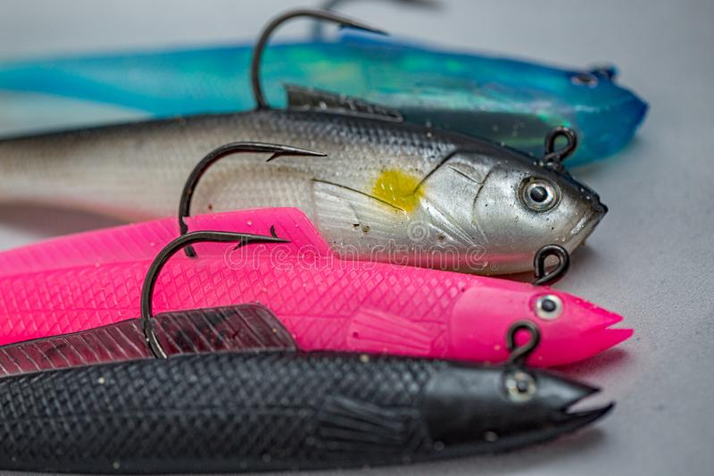 Close up of rubber bass fishing lures, complete with fish hooks, in a row royalty free stock photo