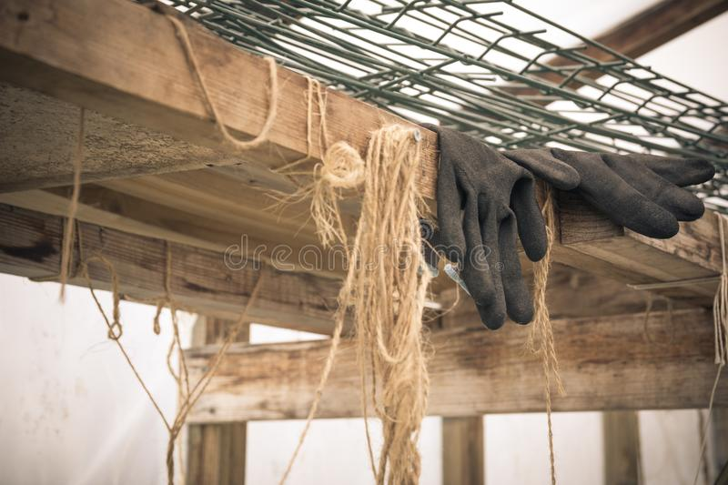 Close up of rubber gloves of a farmer lying in greenhouse. Hard royalty free stock photo