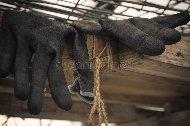 Close up of rubber gloves of a farmer lying in greenhouse. Hard stock images