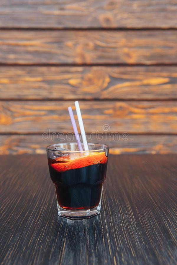 Close-up of rum with cola on a wooden table. wooden background stock image