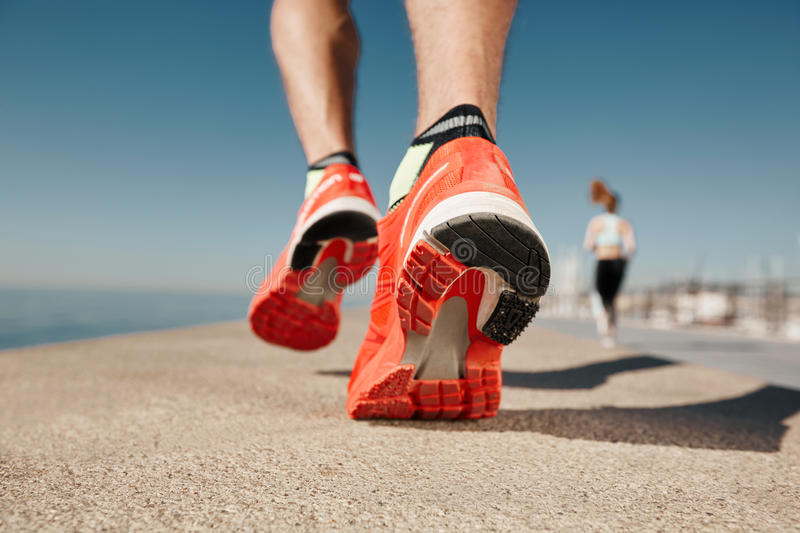 Close up runner feet. Man runner legs and shoes in action on road outdoors at road near sea. Male athlete model stock photography