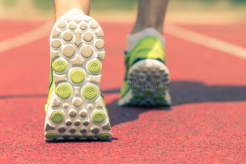 Close up of running shoes in use on the running track. Back side view close up shot of feet with running shoes on the red running track. Jogging, training royalty free stock photography