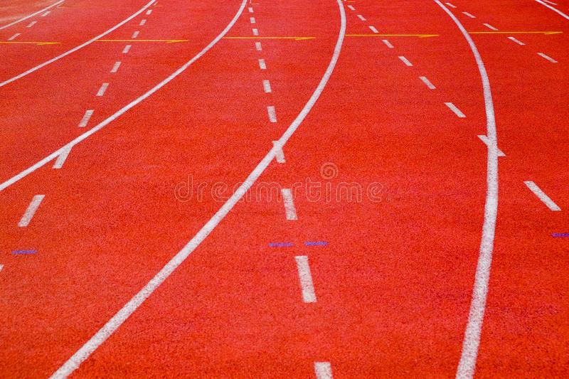 Running track with curve and dash lines. Close-up running track with curve and dash lines on brown field ground arena royalty free stock photo