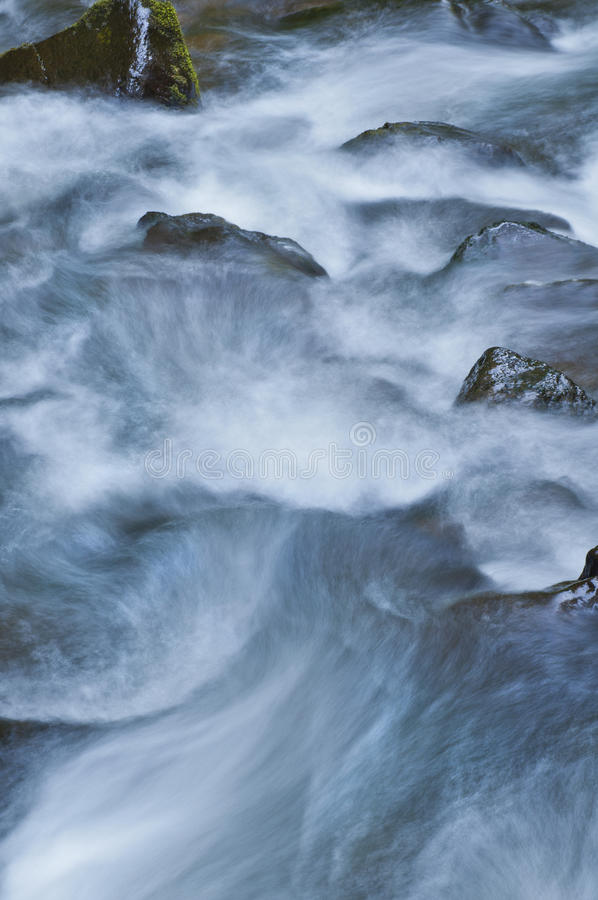 Close up of rushing river water downstream over mossy rocks. Close up of rushing river water flowing downstream in a beautiful pattern stock photo