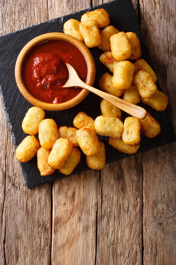 Close up of rustic golden potato tater tots and ketchup. Vertical top view. Close up of rustic golden potato tater tots and ketchup on the table. Vertical top stock photo