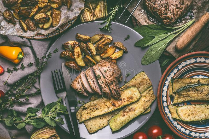 Close up of rustic meal with roasted sliced meat, baked potatoes and vegetables , served on plate with cutlery royalty free stock photography