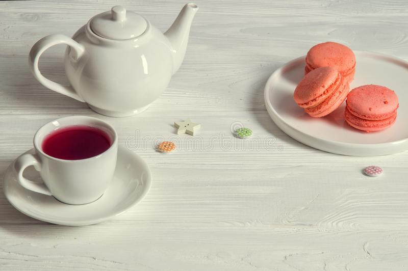Close up. Rustic still life. Provence breakfast. Color living coral. Bright macarons on a round plate. A cup of berry tea, a vintage buttons, a teapot. White royalty free stock images