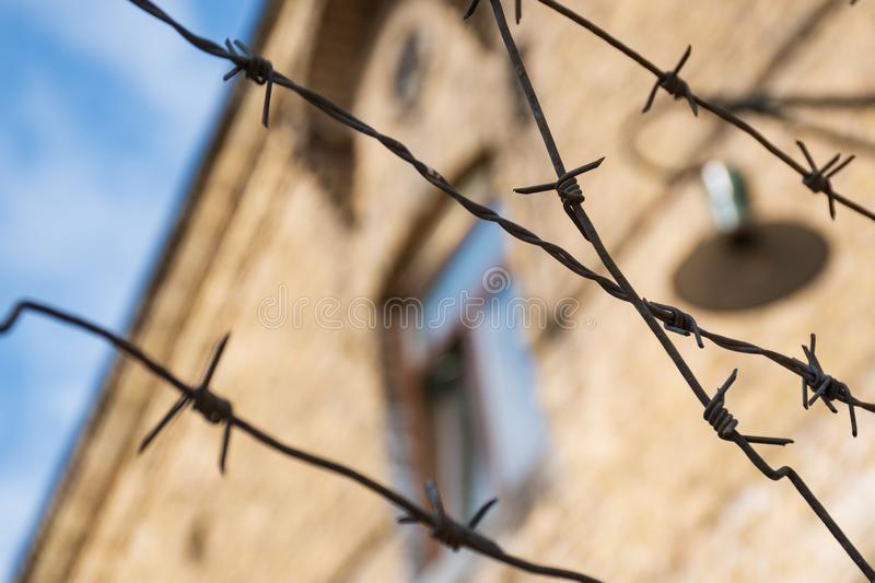 Close-up of a rusty barbed wire fence surrounding a concentration and extermination camp. Old barrack with window and lamp in soft focus in the background royalty free stock photo