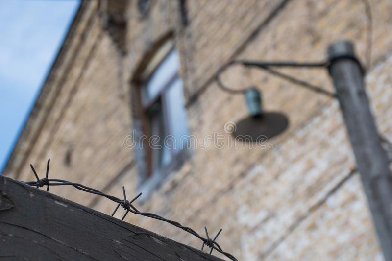 Close-up of a rusty barbed wire fence surrounding a concentration and extermination camp. Old barrack with window and lamp in soft focus in the background royalty free stock photos