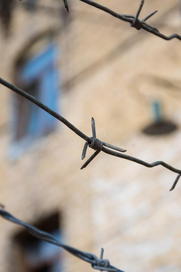 Close-up of a rusty barbed wire fence surrounding a concentration and extermination camp. Old barrack with window and lamp in soft focus in the background royalty free stock photography