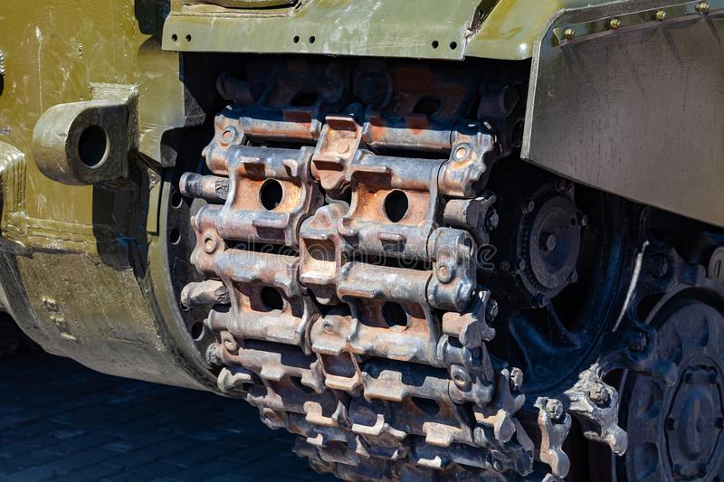 Close-up on a rusty old caterpillar of a green tank worn on wheels standing on the road. Military equipment for the murder and the stock image