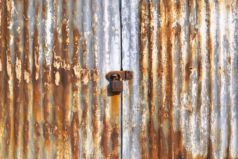 Close-up rusty old corrugated iron doors with padlock. Close-up of rusty weathered old corrugated iron doors with padlock background stock image