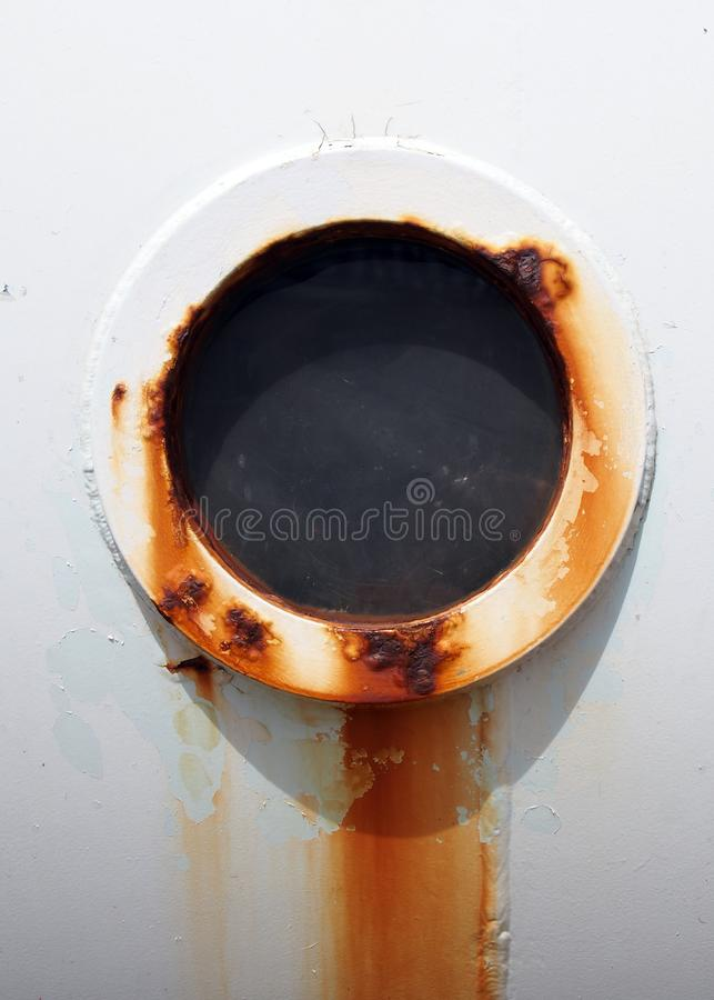 Close up of a rusty streaked round round porthole in the side of an old white painted iron ship royalty free stock images