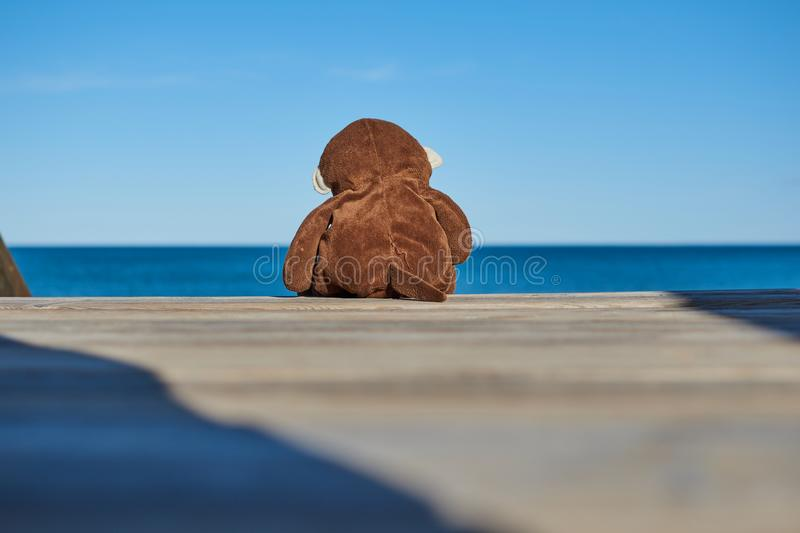 Close-up of a sad brown toy monkey and alone sitting on a wooden ladder going down to the beach looking pensively in the backgroun royalty free stock image