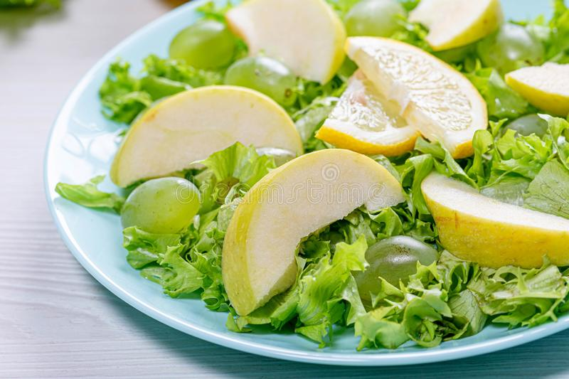 Close-up of salad with apples, grapes and lettuce in a blue plate & x28;Flip 2019 royalty free stock photography