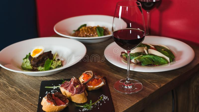 Close-up salad with grilled beef meat and boiled egg, bread with hummus and jamon near. Dinner at restaurant royalty free stock image