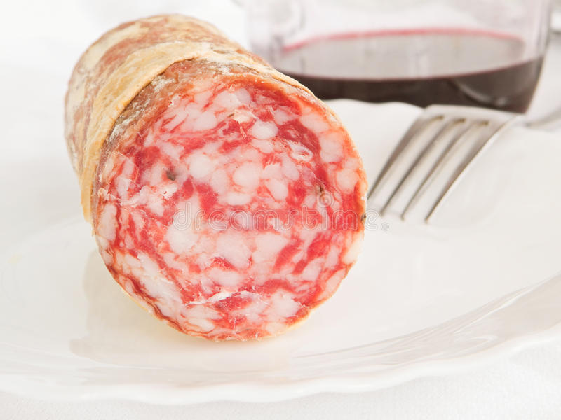 Close up of salami on white dish. Salami with fork and red wine pitcher in background royalty free stock photos