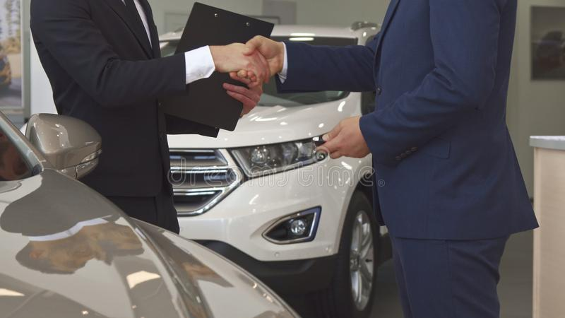 Sales manager sells car to the customer at the dealership stock photo