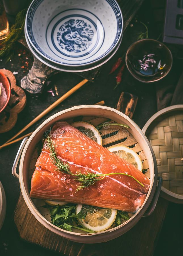 Close up of salmon fillet in asian bamboo steamer with lemon slices and dill on kitchen table, top view. Raw salmon. Cooking. Preparation. Healthy food. Keto royalty free stock photo