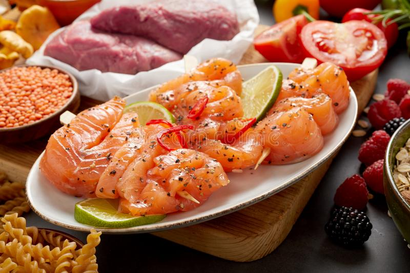 Salmon skewers and assorted healthy paleo foods stock photography