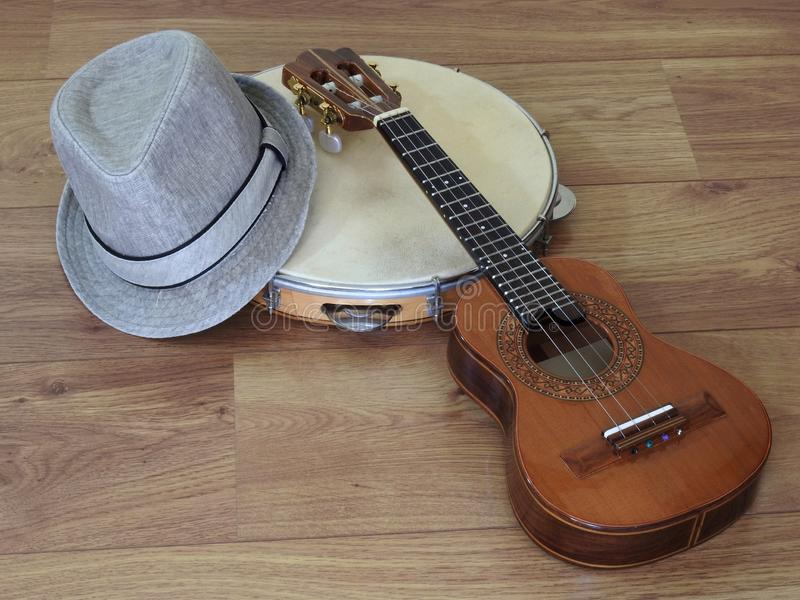 Close-up of a samba player sambista hat and two Brazilian musical instruments: cavaquinho and pandeiro tambourine. stock photo