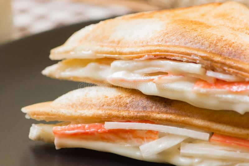 Close up of sandwich stuffed with salad sauce and crab stick in black dish royalty free stock photography
