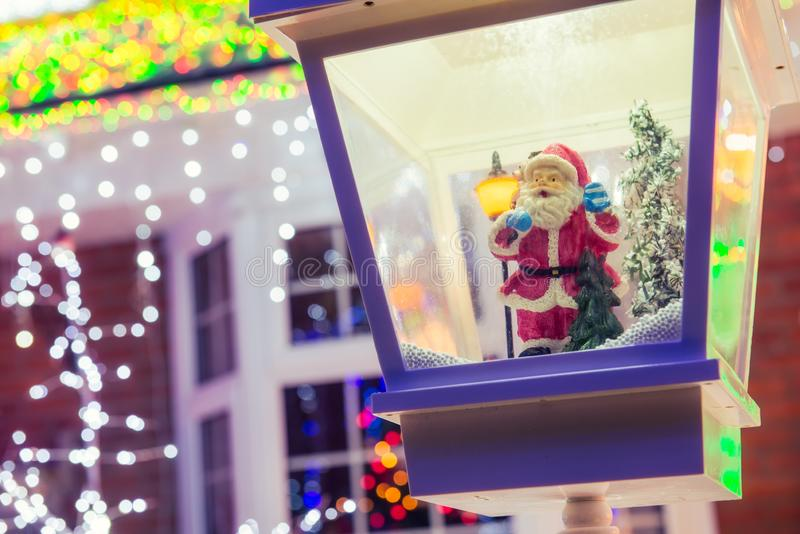 Close up Santa Claus in decorative lantern in the snow on the blurred Christmas Lights Background and outdoor decorations. Merry royalty free stock images