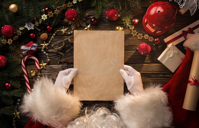 Santa Claus hands holding blank letter. Close up of Santa Claus hands holding blank letter with copy space royalty free stock photos