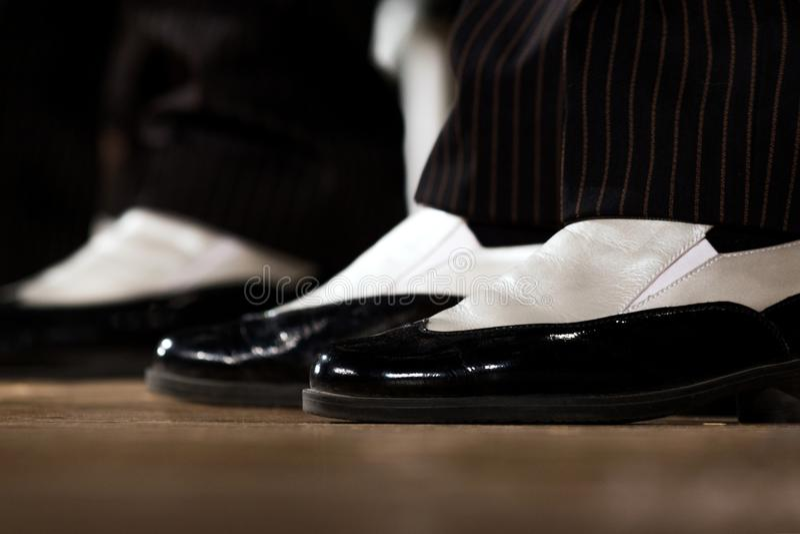 Close-up Sapatas preto e branco à moda a executar na fase nos pés dos homens fotos de stock royalty free