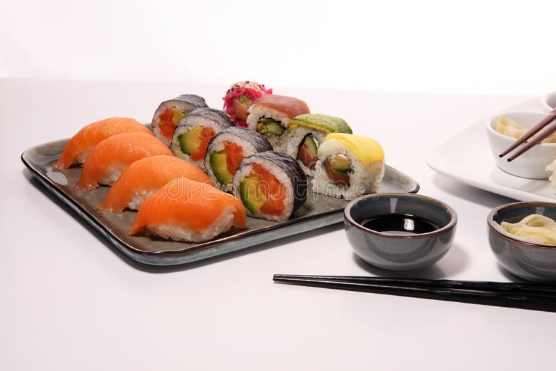 Close up of sashimi sushi set with chopsticks and soy - sushi roll with salmon and sushi roll with smoked eel. Selective focus royalty free stock images
