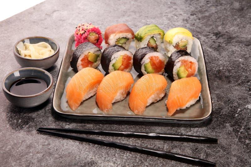 Close up of sashimi sushi set with chopsticks and soy - sushi roll with salmon and sushi roll with smoked eel. Selec.tive focus royalty free stock images