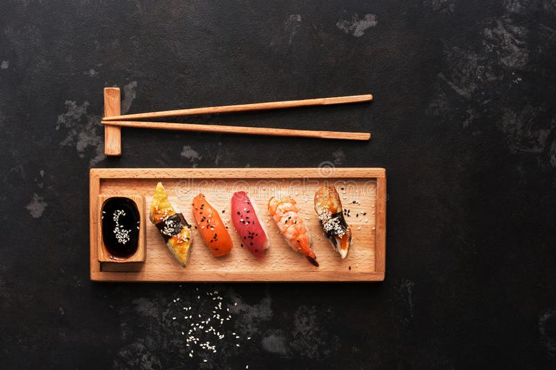Close up of sashimi sushi set with chopsticks and soy sauce, dark stone background. Top view, copy space stock images