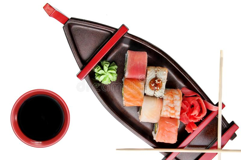 close up of sashimi sushi set with chopsticks and soy on a serving boat tray isolated on white royalty free stock image