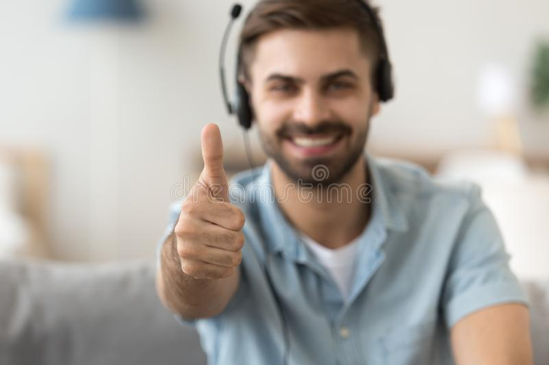Close up satisfied man in headset showing thumbs up, approval. Close up satisfied man in headset showing thumbs up, sitting on couch at home, approval, smiling stock image