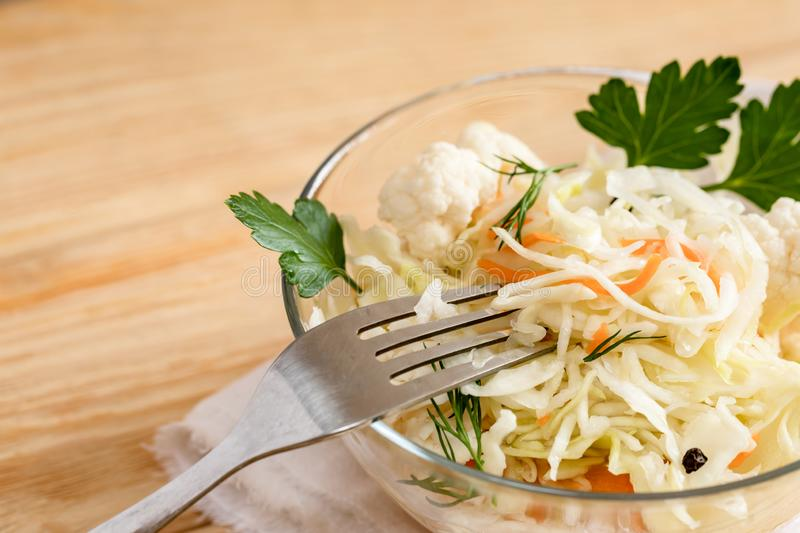 Close-up sauerkraut and fork in glass bowl is standing on light wooden table. royalty free stock photos