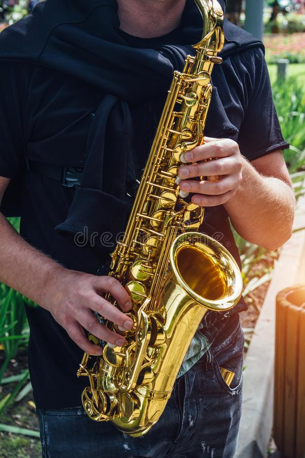 Close up of saxophone player`s hands playing jazz music stock image