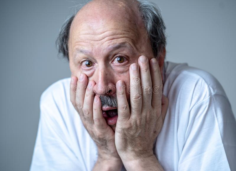 Close up of scared and shocked senior man gesturing in fear with hands and face royalty free stock image