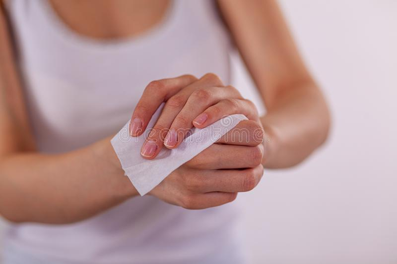 Close up cleaning hands with wet wipes. Close up scene woman cleaning hands with wet wipes, white royalty free stock photo