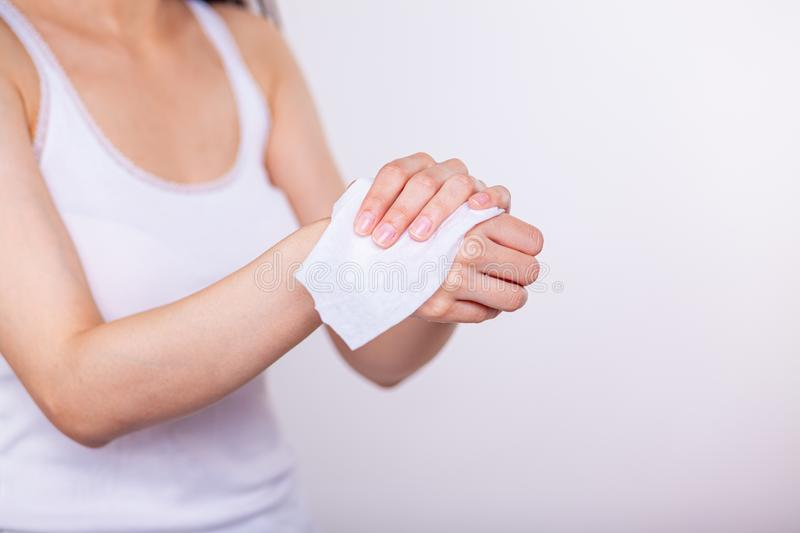 Close-up scene: Women cleaning hands with wet wipes. Close-up scene: Young woman cleaning hands with wet wipes, white background, studio shot stock images