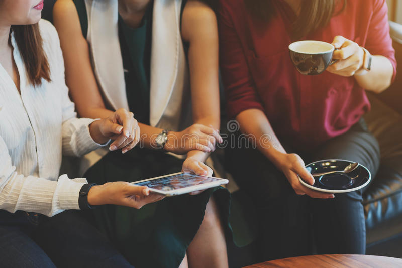 Close up scene of 3 woman using tablet together in coffee shop royalty free stock photography
