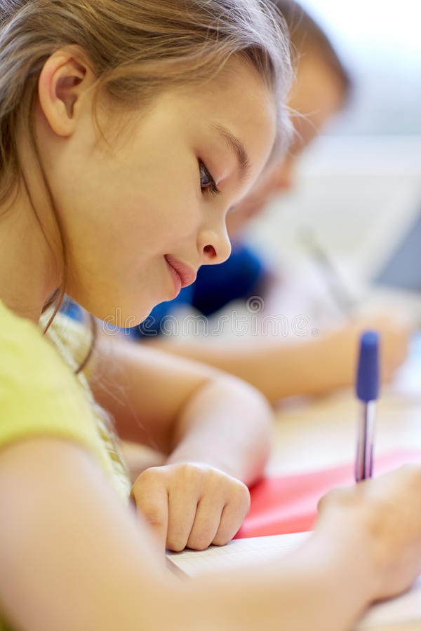 Close up of school kids writing test in classroom royalty free stock photo